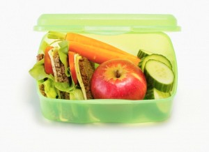 Healthy lunch box containing sandwiches, apples, vegetables