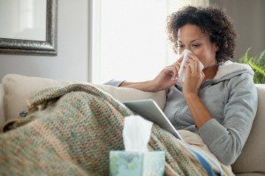 Woman nursing a cold at home.